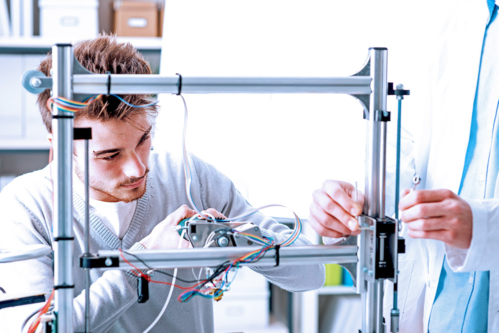 Engineers in a lab use a 3D printer