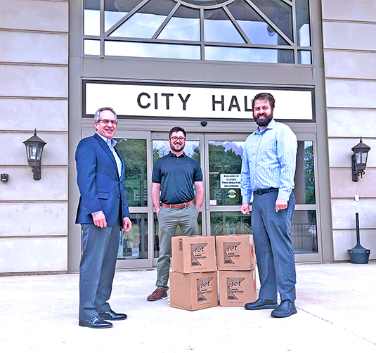 Michael Bowling and Yazz Krdzalic pictured with Mayor David Still and four boxes of hand sanitizer at Lawrenceville City Hall