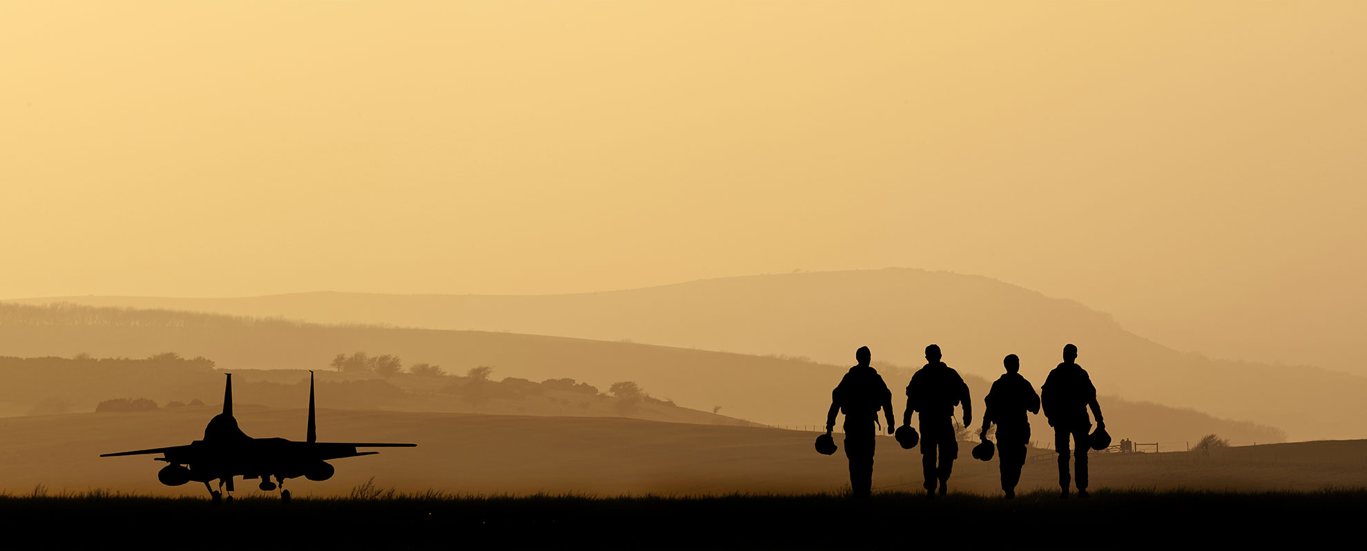 Silhouette: Four pilots stroll past an aircraft.