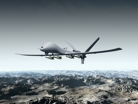 Military drone flying over a mountain range
