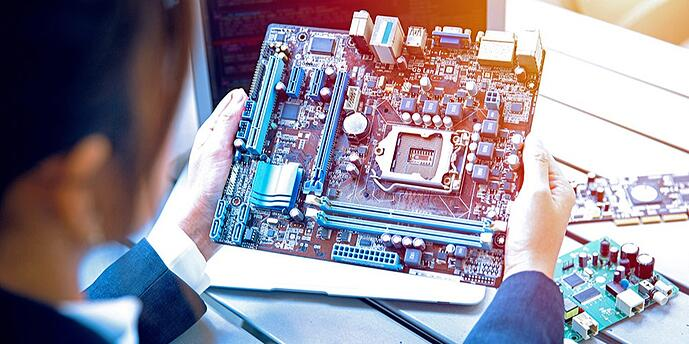 This is a photo of a person holding a printed circuit board (PCB).