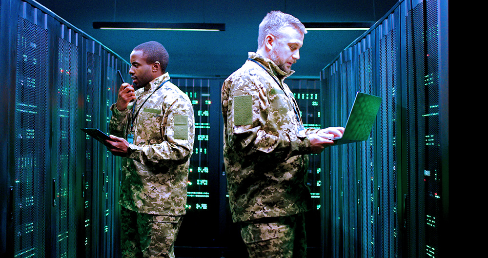 Two servicemembers appear frustrated as they investigate a military server room