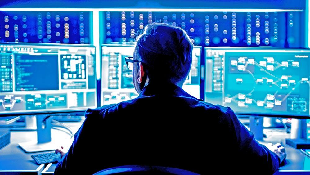 A man looking at three computer monitors