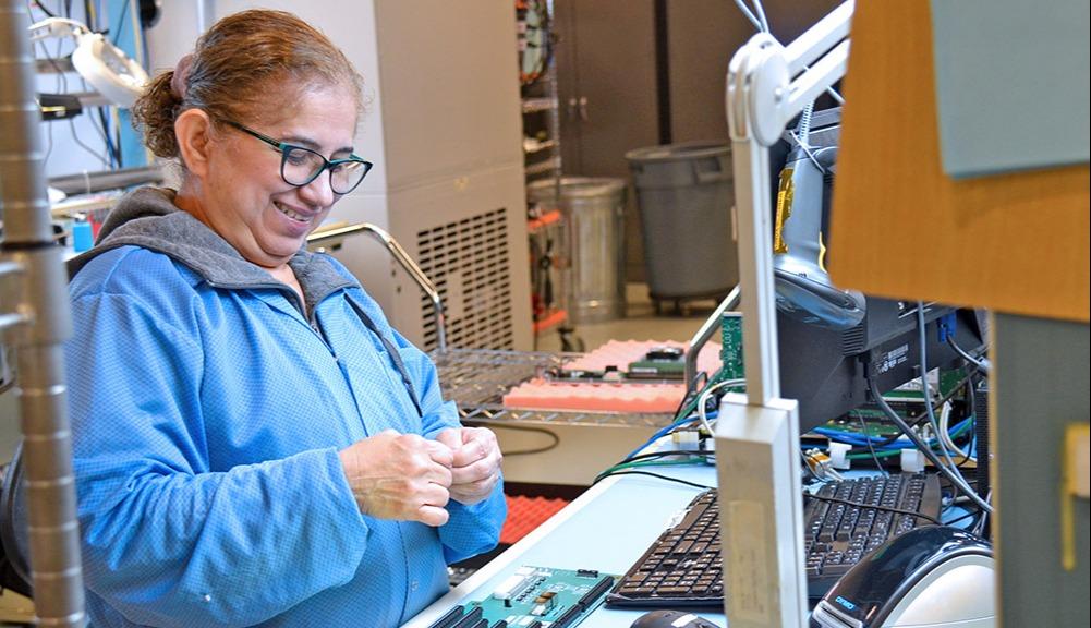 Maritza De Jesus, assembly technician at Trenton Systems, laughs as she works on a Trenton processor board.