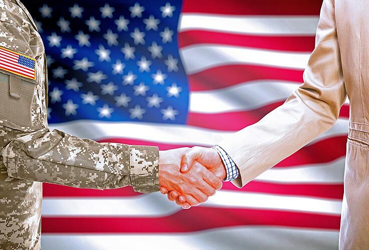 Military officer shaking hands with businessperson