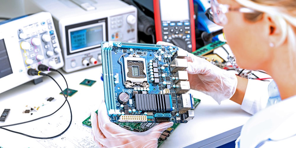 This is a photo of an electrical engineer examining a motherboard.