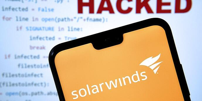 """The SolarWinds app appears on a cellphone in front of a monitor that reads """"hacked"""""""