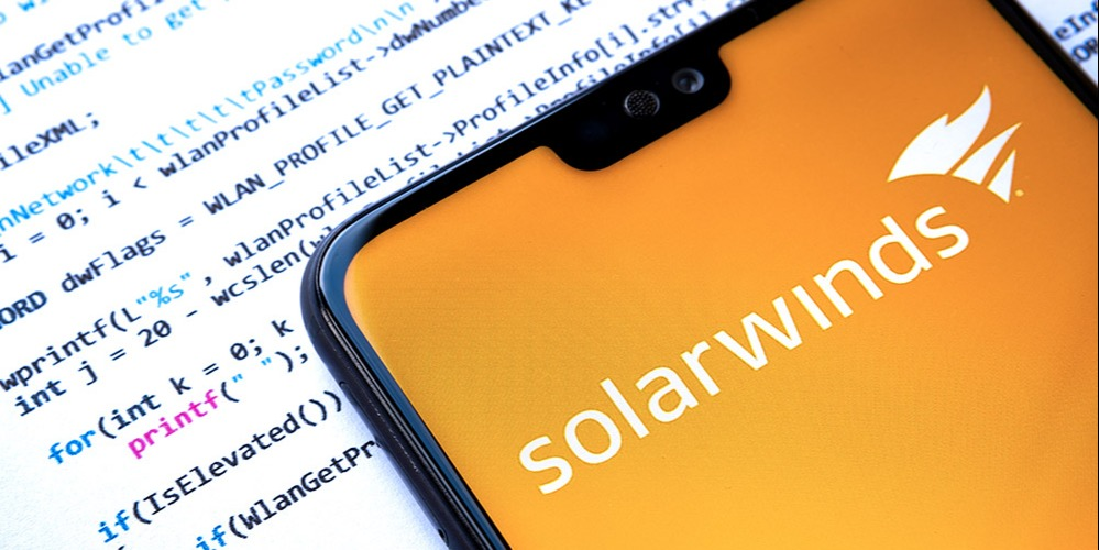 The SolarWinds app appears on a phone, which is laid upon a paper containing lines of code