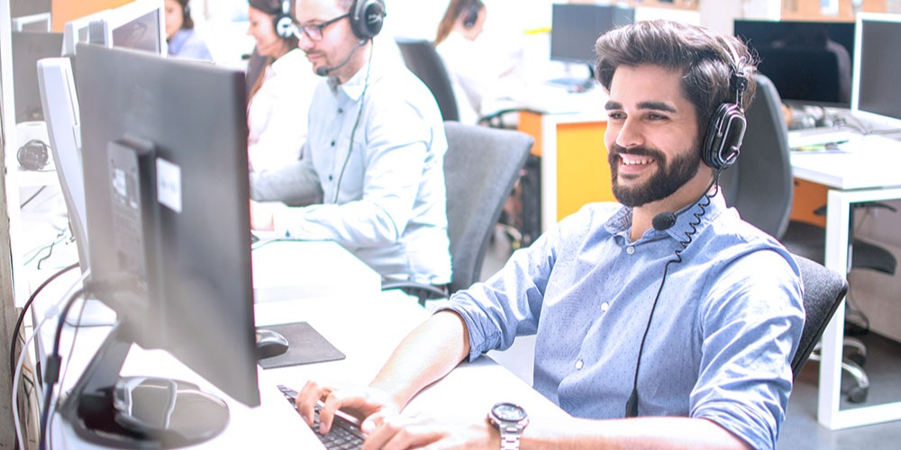 A technical support agent smiles while interacting with a customer