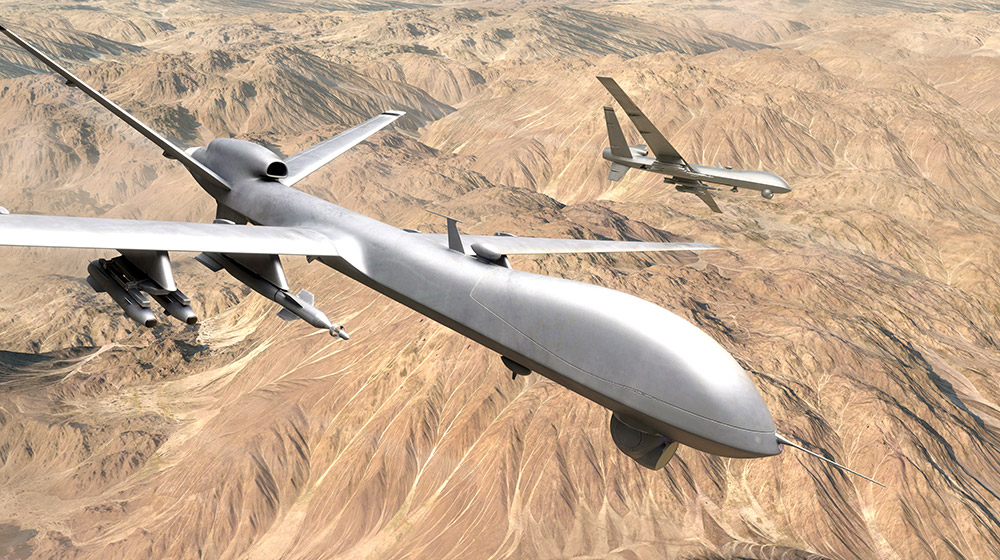 Two UAVs hover over a desert